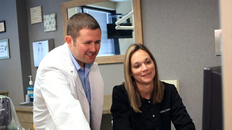 Dr. Glasscock and Staff member smiling and looking at computer screen