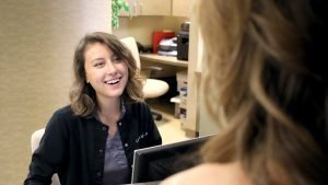 staff member smiling as seen over patient shoulder